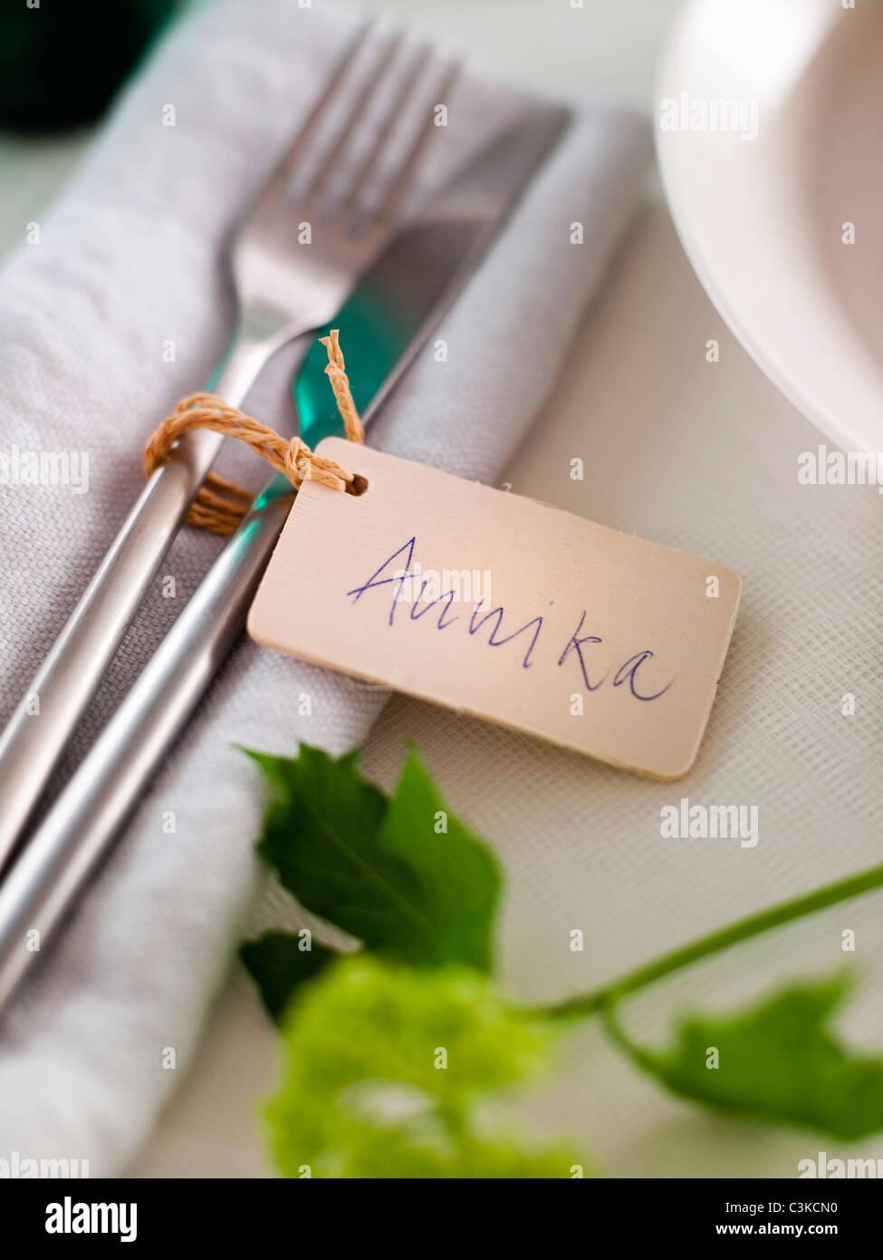 Besteck auf Serviette mit Tischkarte Stockbild