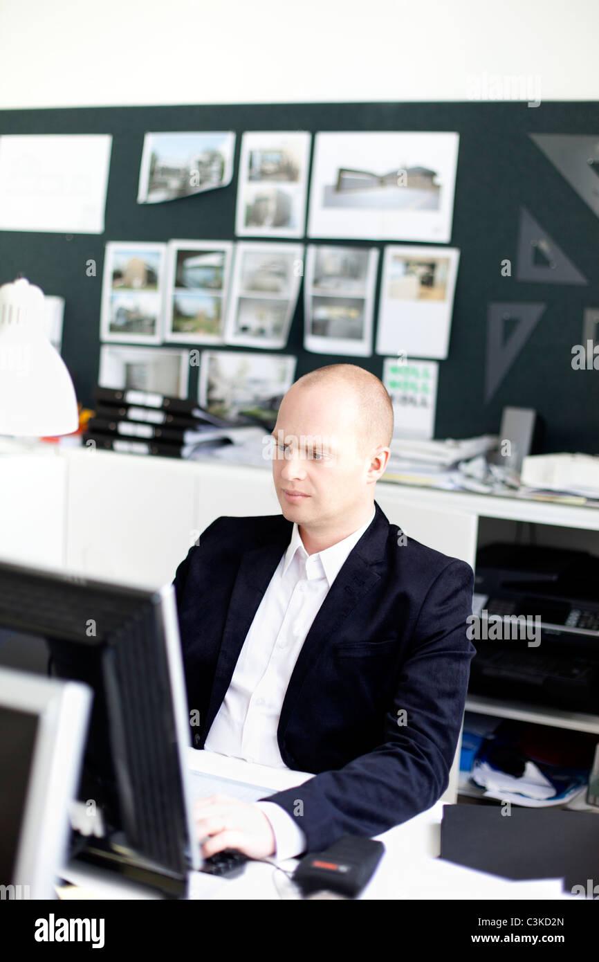 Mann sitzt im Büro mit computer Stockbild