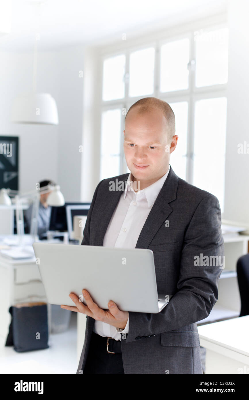 Mann im Amt halten laptop Stockbild