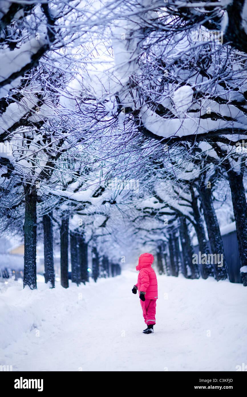 Kind im verschneiten park Stockbild