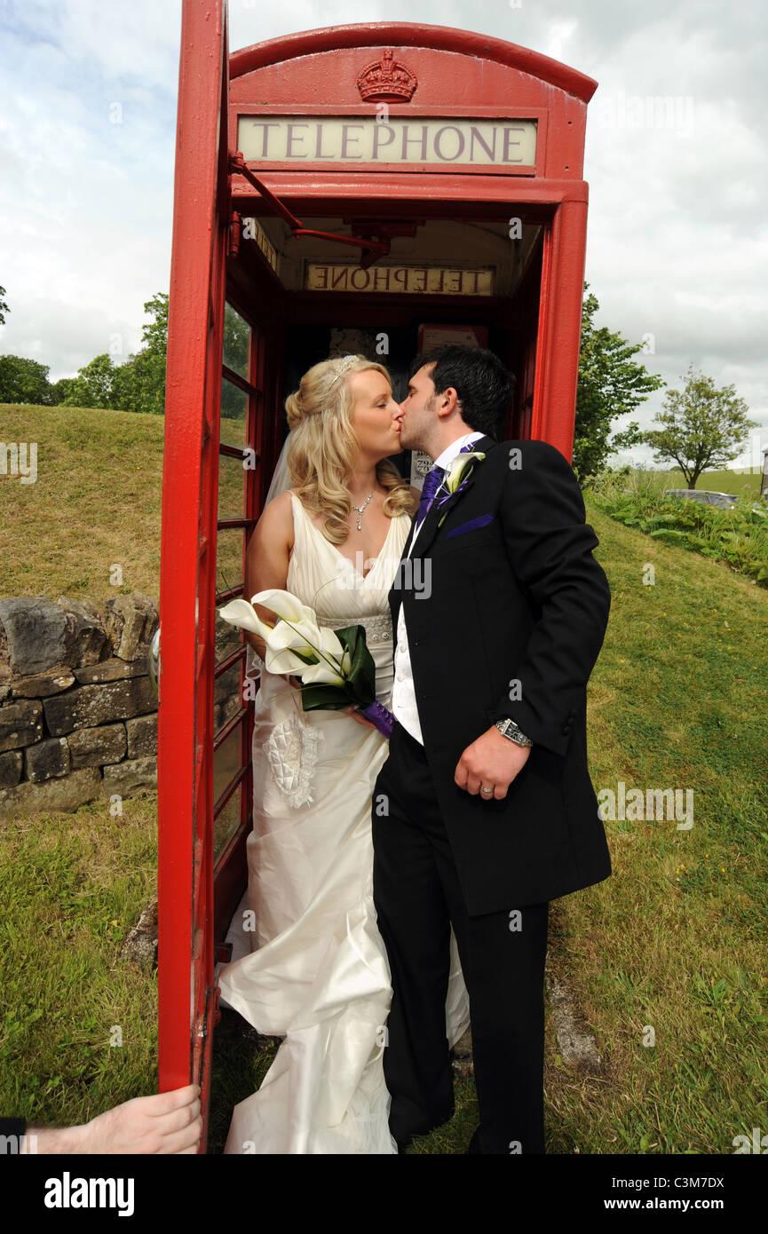 Britische traditionelle Braut und Bräutigam küssen in eine traditionelle rote Telefonzelle am Tag ihrer Stockbild
