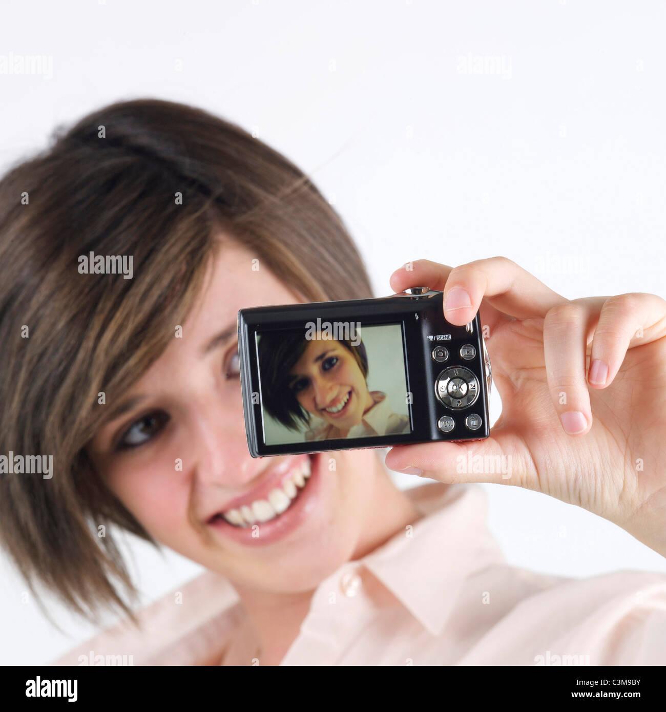 Junge Frau, die ein Foto von sich selbst mit einer Kamera Stockbild