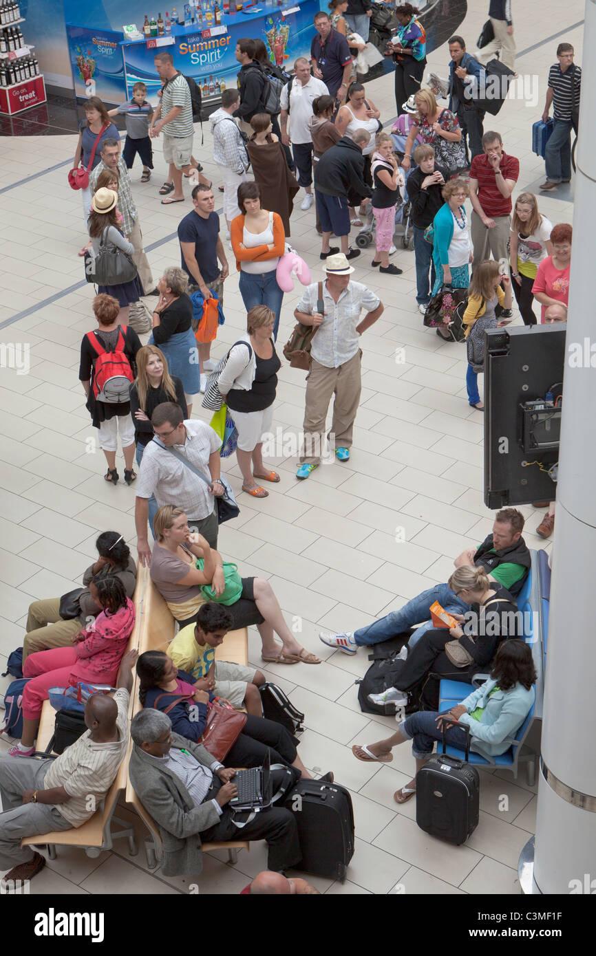 Passagiere warten auf Fluginformationen in der Abflughalle des Südens terminal am Flughafen Gatwick, England Stockbild