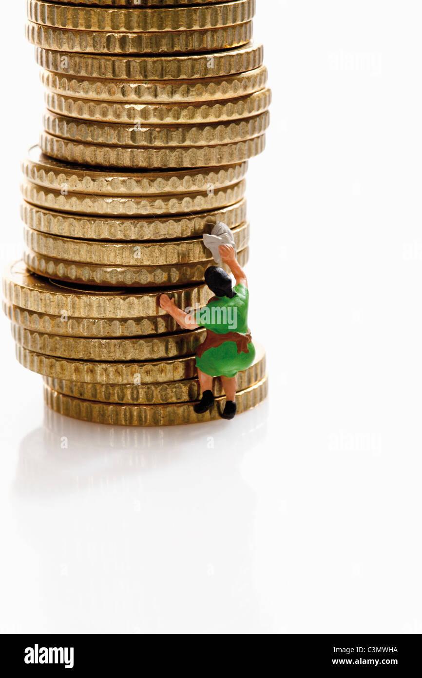 Frau Figur Reinigung Stapel von Münzen Stockbild
