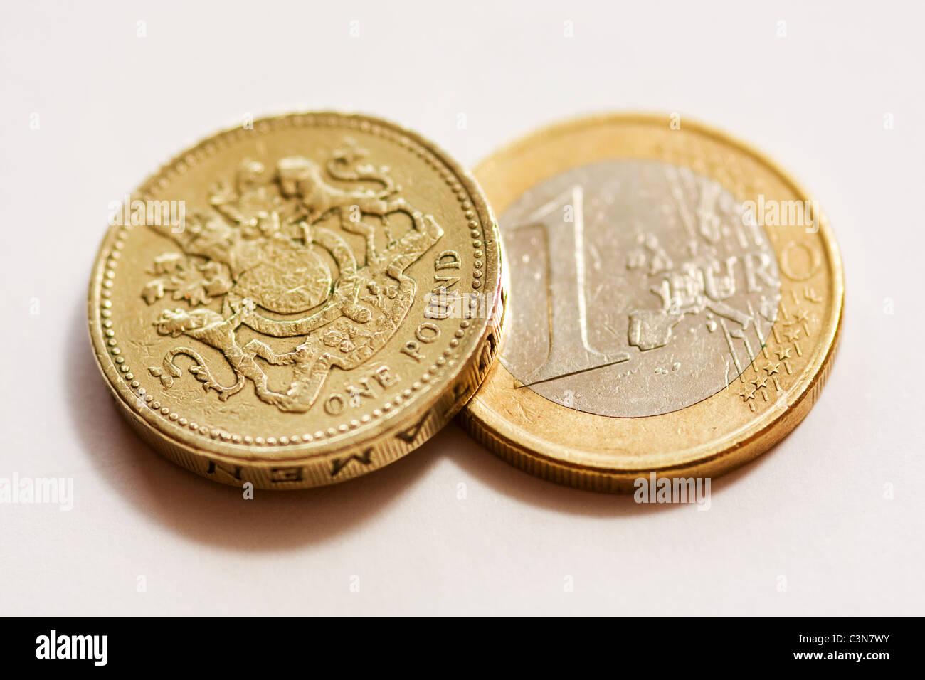 Ein Pfund-Münze mit einem ein-Euro-Münze Stockbild