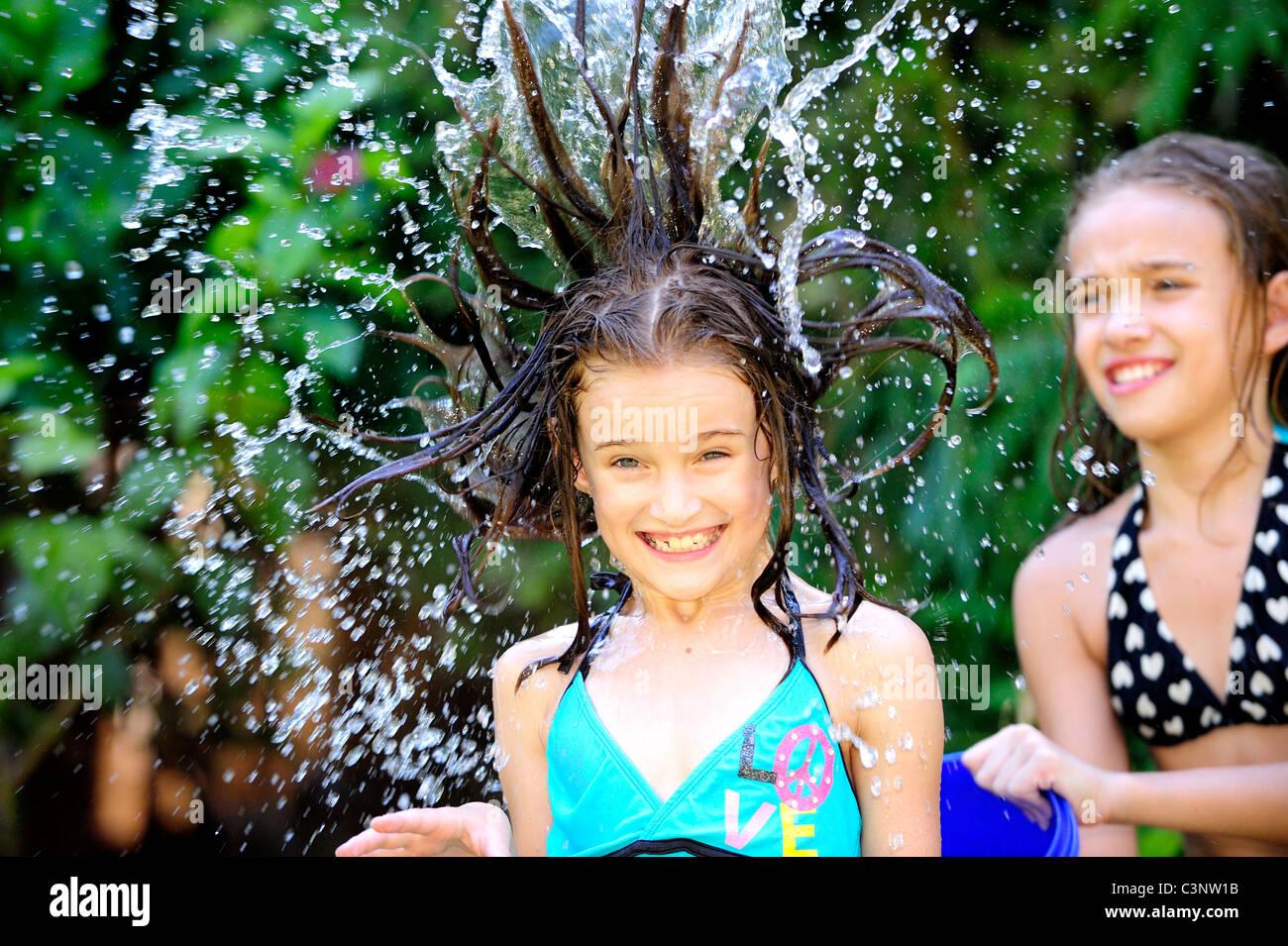 Kind (12 Jahre alt) werfen Eimer Wasser über ihre Schwester (9 Jahre alt) Stockbild