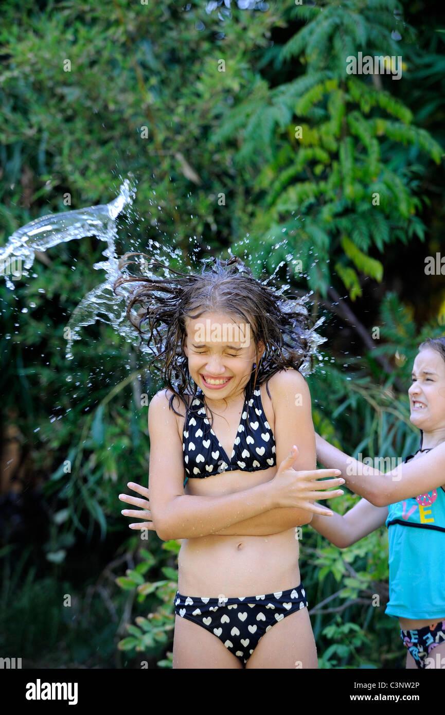 Kind (9 Jahre alt) werfen Eimer Wasser über ihre Schwester (12 Jahre alt). Stockbild
