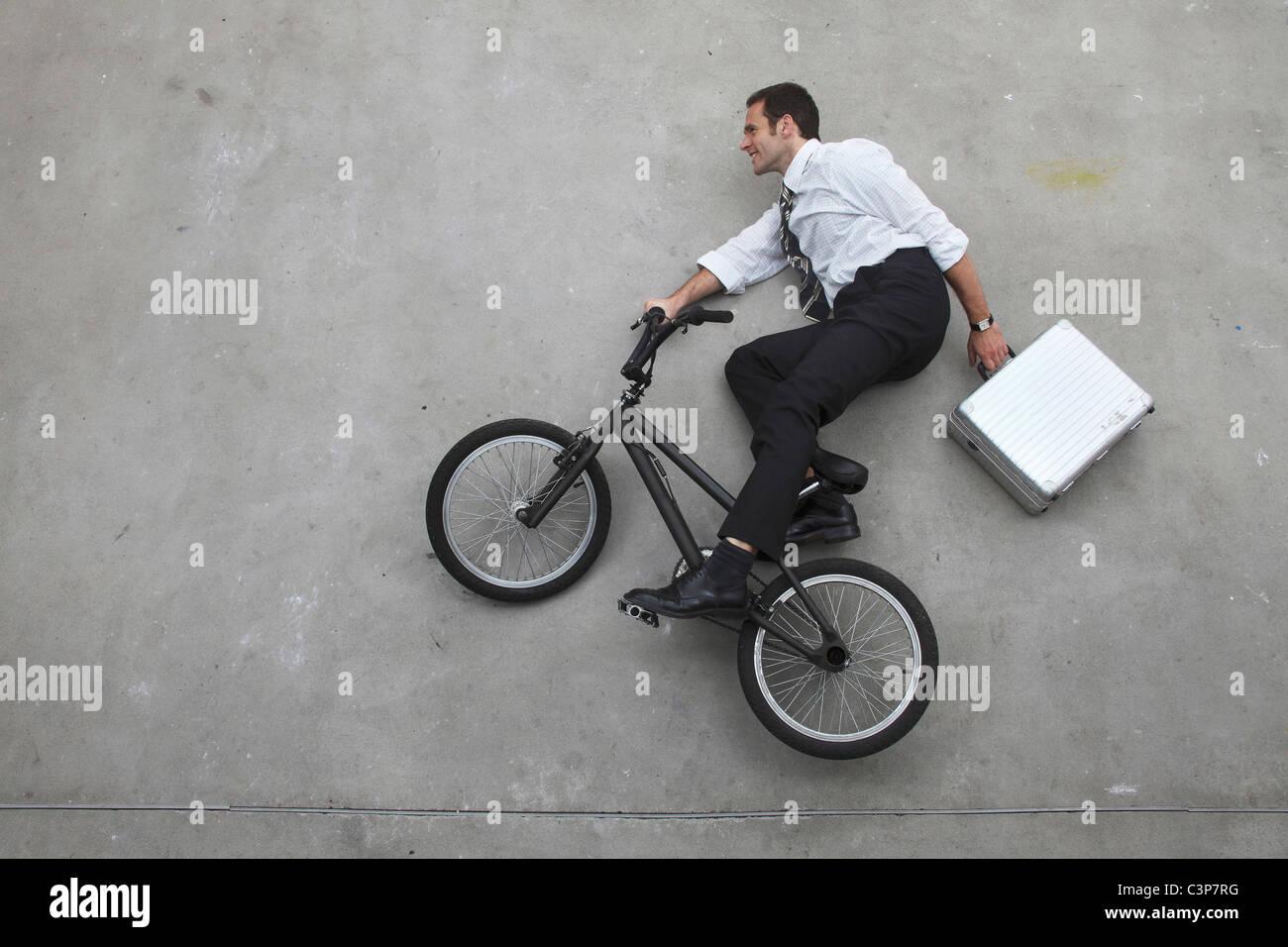 Geschäftsmann Reiten Fahrrad Holding Koffer, erhöhten Blick Stockbild