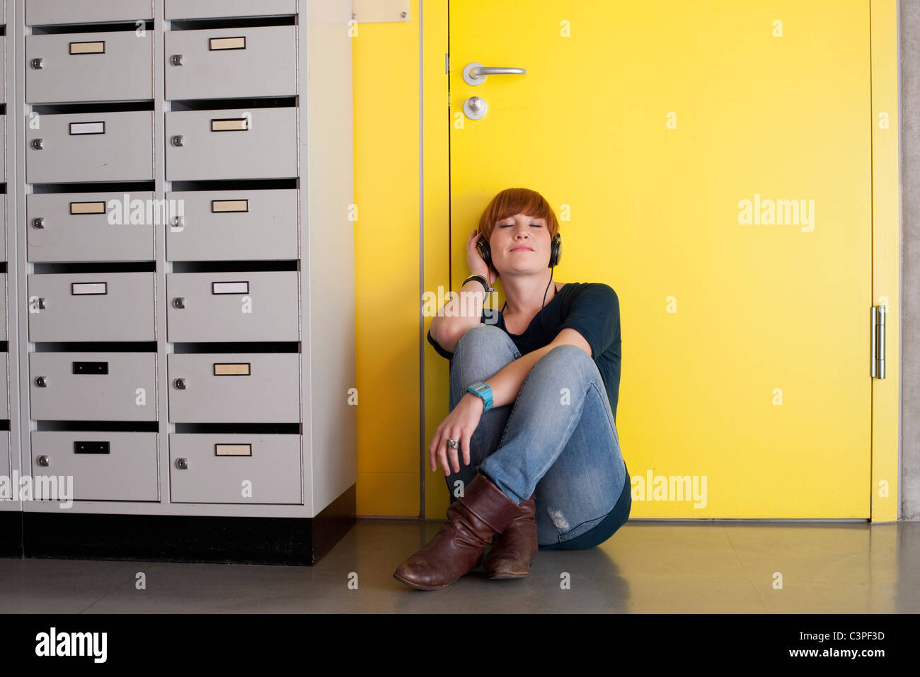 Deutschland, Leipzig, junge Frau sitzen und hören Sie Musik in Umkleidekabine Stockbild