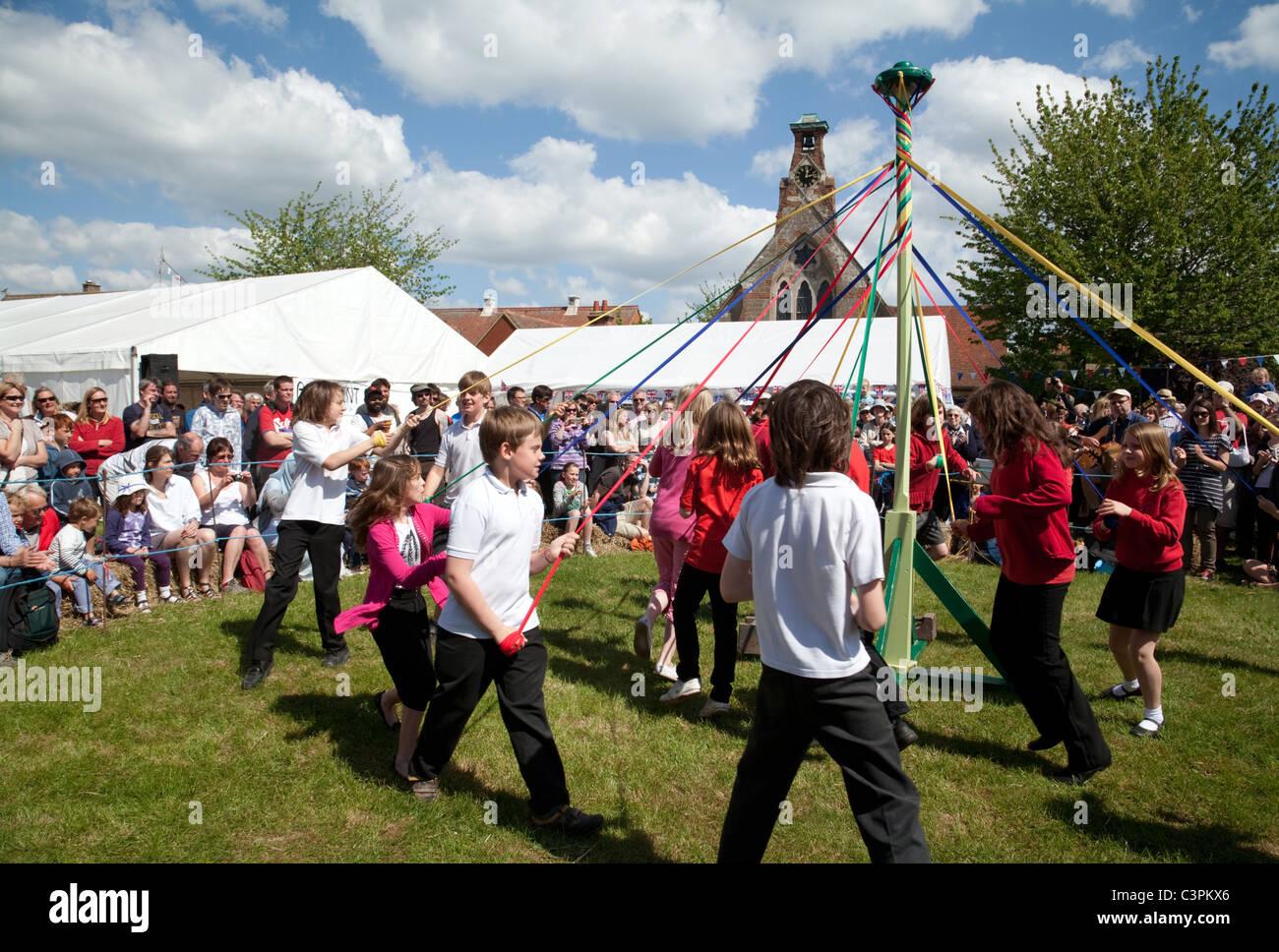 Kinder aus einer örtlichen Grundschule Tanz runden den Maibaum am Maifeiertag zu erreichen Fair, Reach, Cambridgeshire, Stockbild