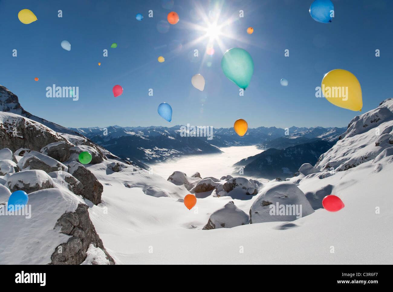 Ballons fliegen über verschneite Winterlandschaft Stockbild