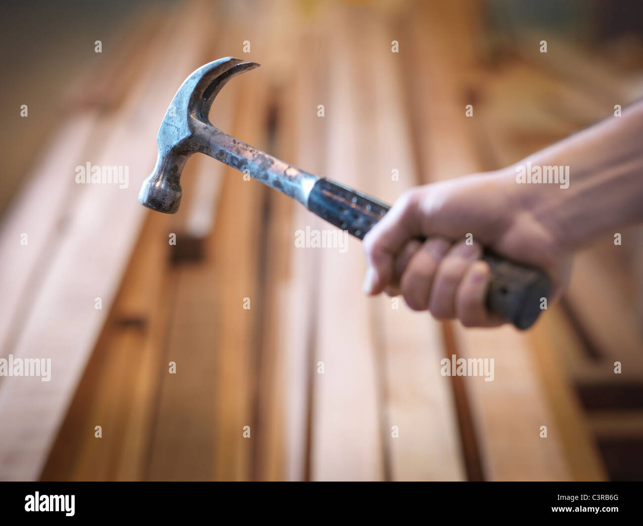Hand mit Hammer neben Holz Stockbild