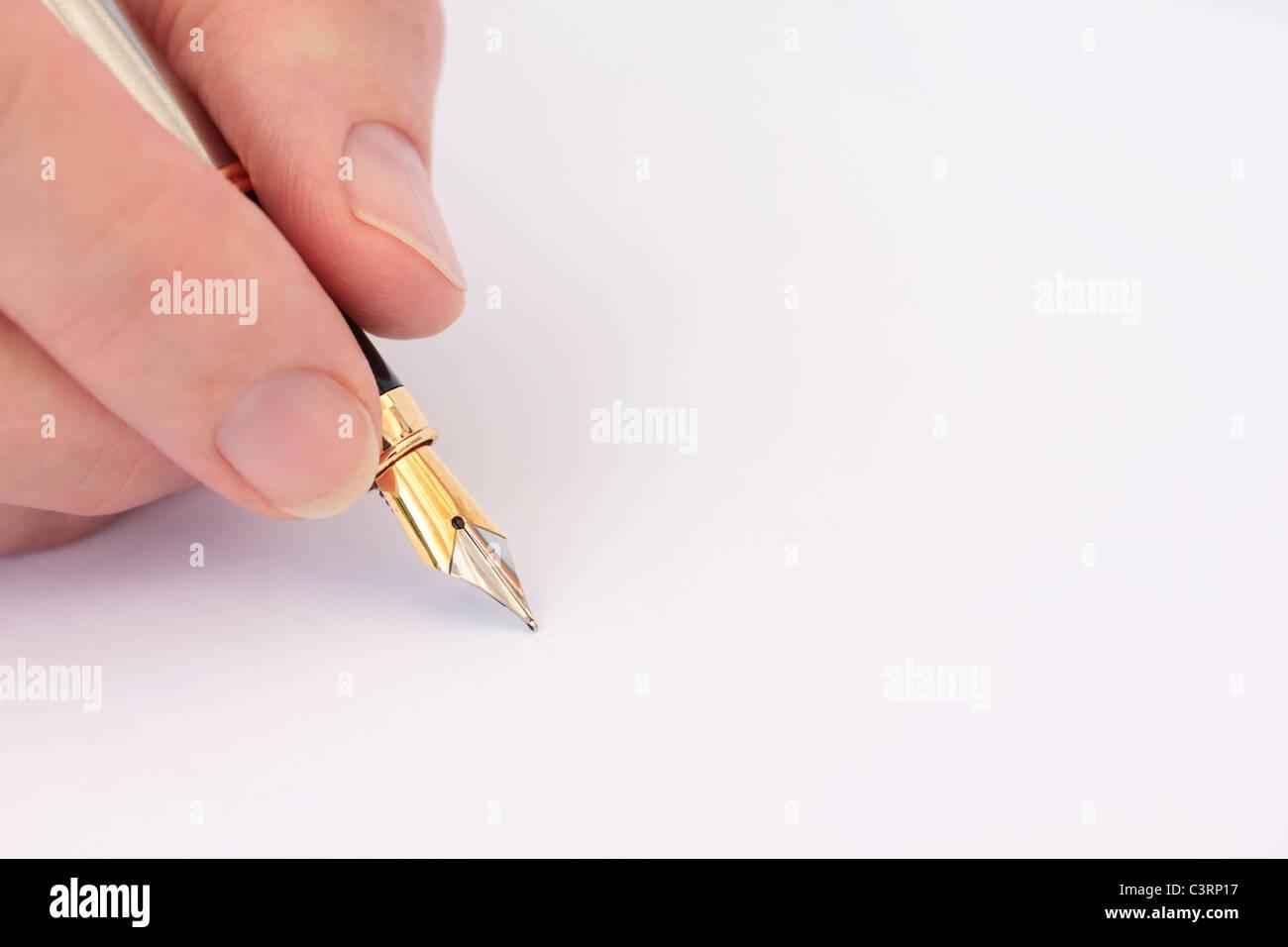 Hand mit Füllfederhalter auf Blankopapier Closeup Stockbild