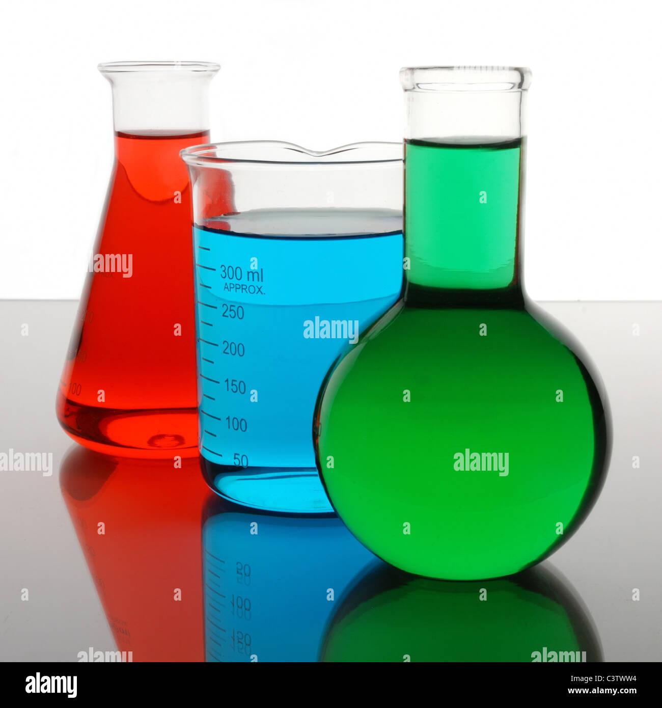 Labor-Becher und Flaschen, die rote, blaue, grüne Flüssigkeiten enthalten Stockbild