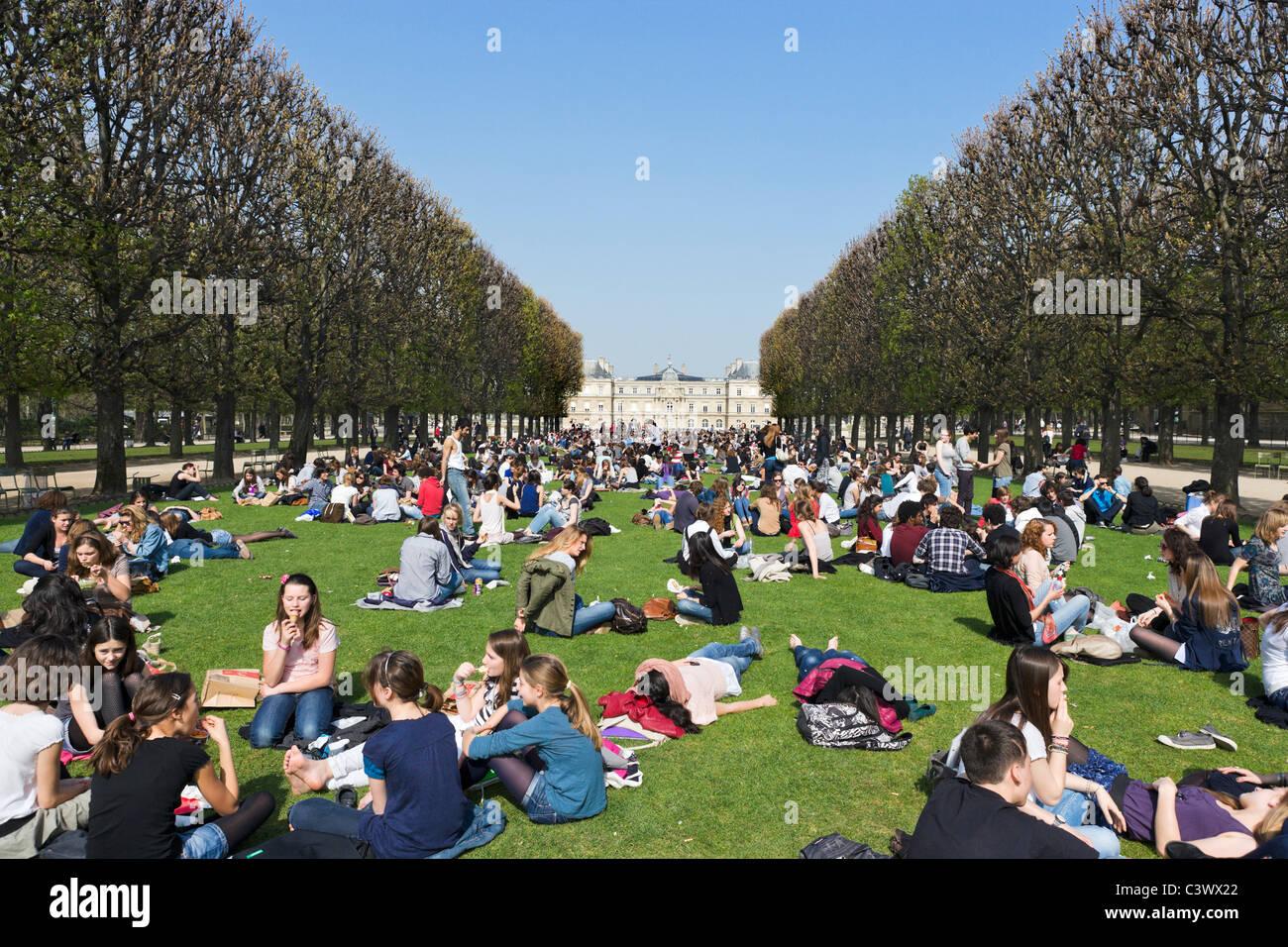 Schüler mit Mittagessen auf dem Rasen vor dem Palais du Luxembourg im frühen Frühlingssonnenschein, Stockbild