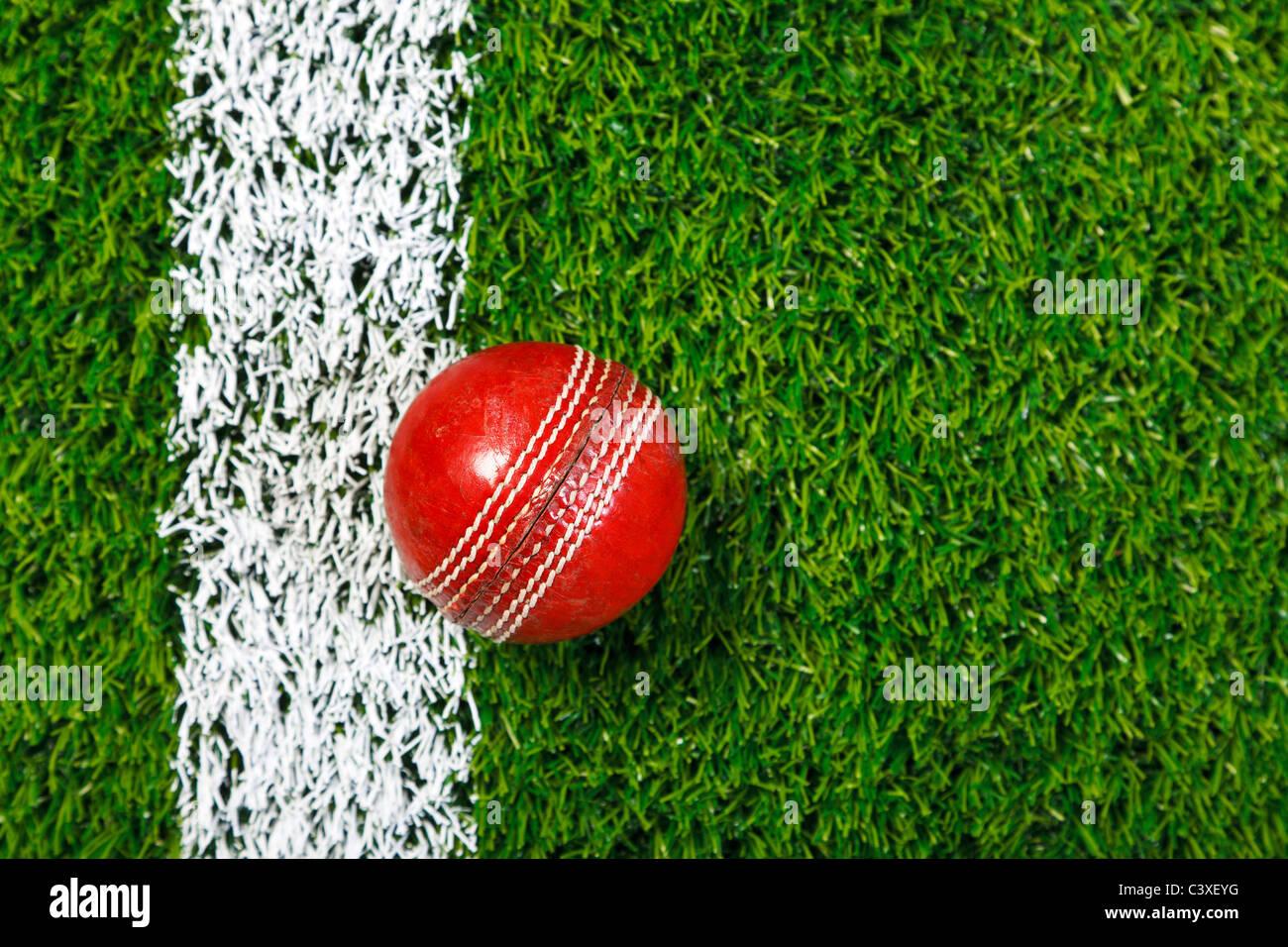 Foto von ein Cricketball auf einer Wiese neben der weißen Linie, von oben geschossen. Stockbild