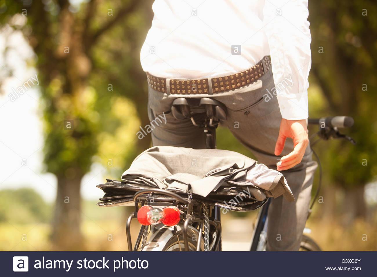 Nahaufnahme von Mantel und Aktenkoffer auf Rückseite des jungen Geschäftsmann Fahrrad Stockbild