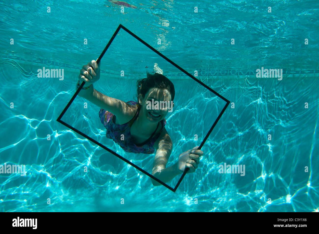 Teenager-Mädchen halten Bilderrahmen unter Wasser im Schwimmbad ...