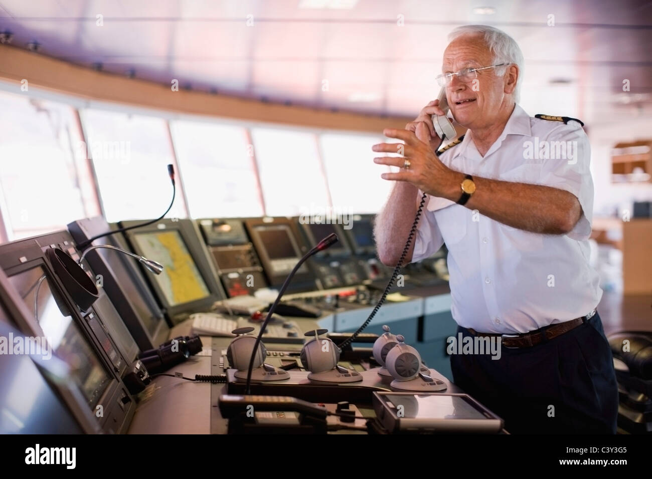Kapitän eines Schiffes mit einem Anruf Stockbild