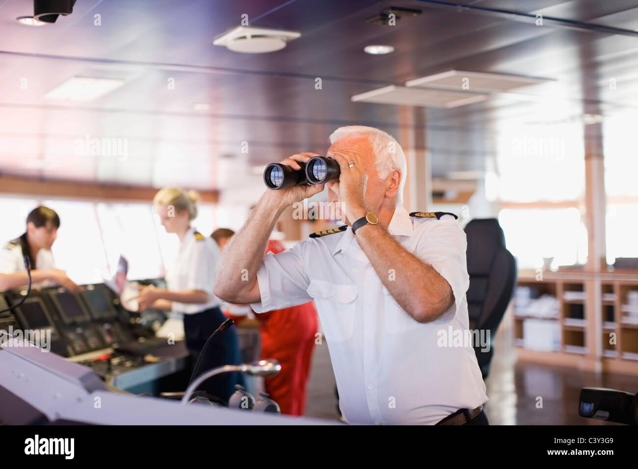 Kapitän auf Schiff Blick durch ein Teleskop Stockbild