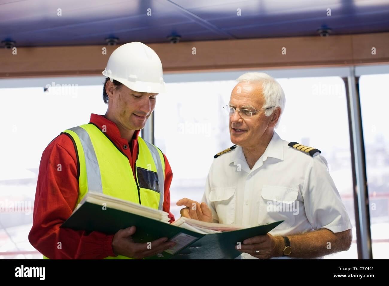 Kapitän ein Schiff mit einer Arbeit zu diskutieren Stockbild
