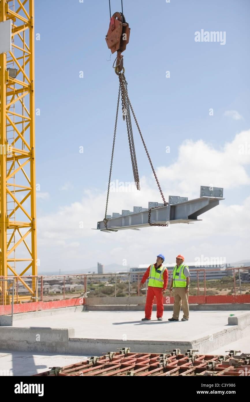 Kran und Arbeiter auf der Baustelle Stockbild
