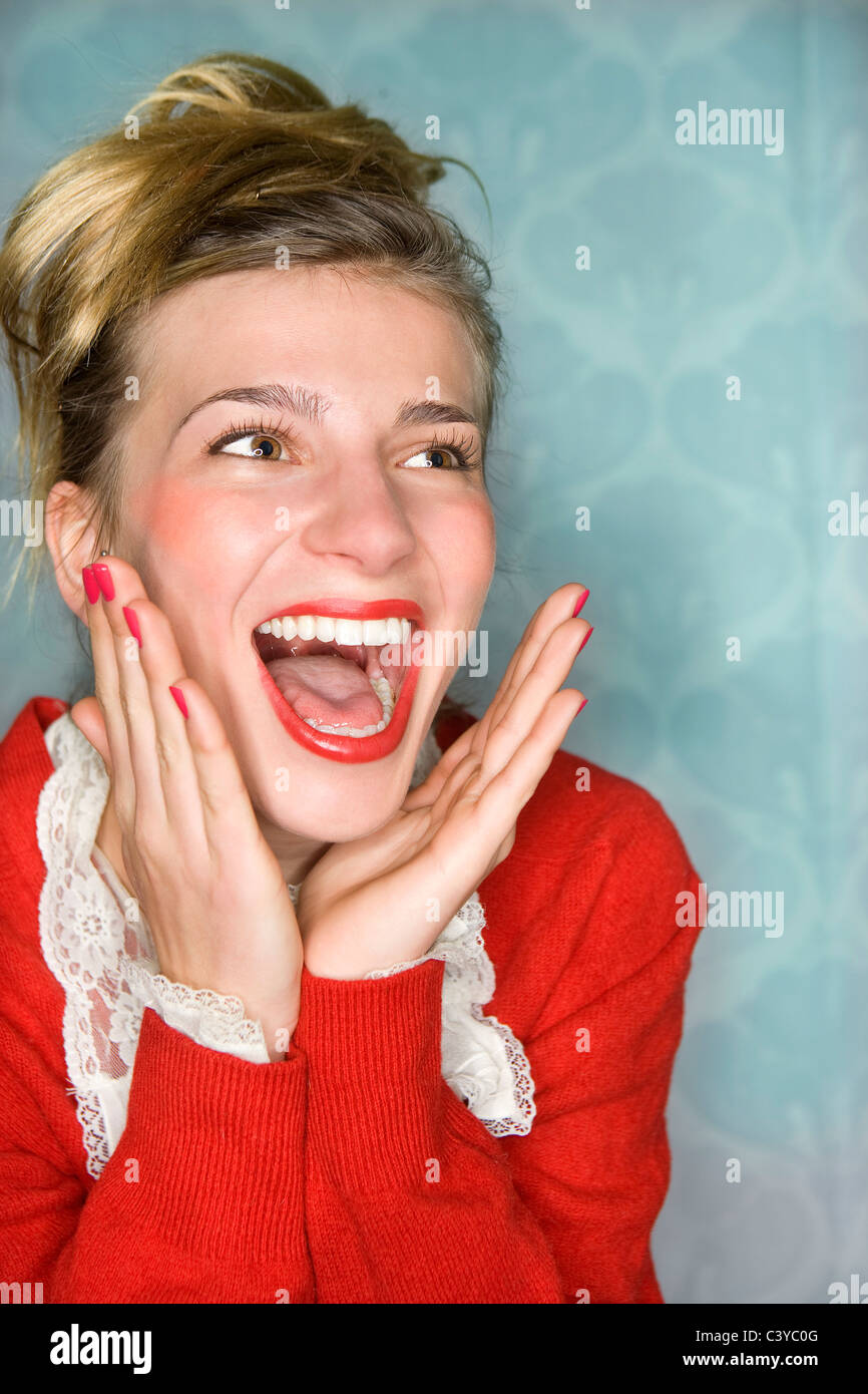 Junge Frau freudige Überraschung Hände hoch, rot Stockbild