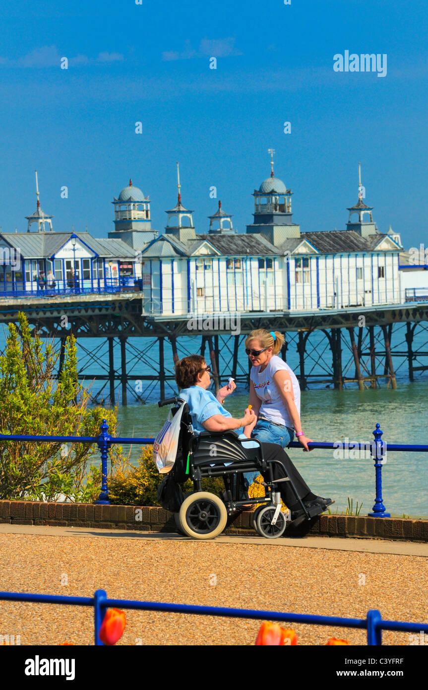 Ältere Frau in einem Rollstuhl im Chat mit einer jüngeren Frau auf Eastbourne Strandpromenade, East Sussex, UK Stockfoto