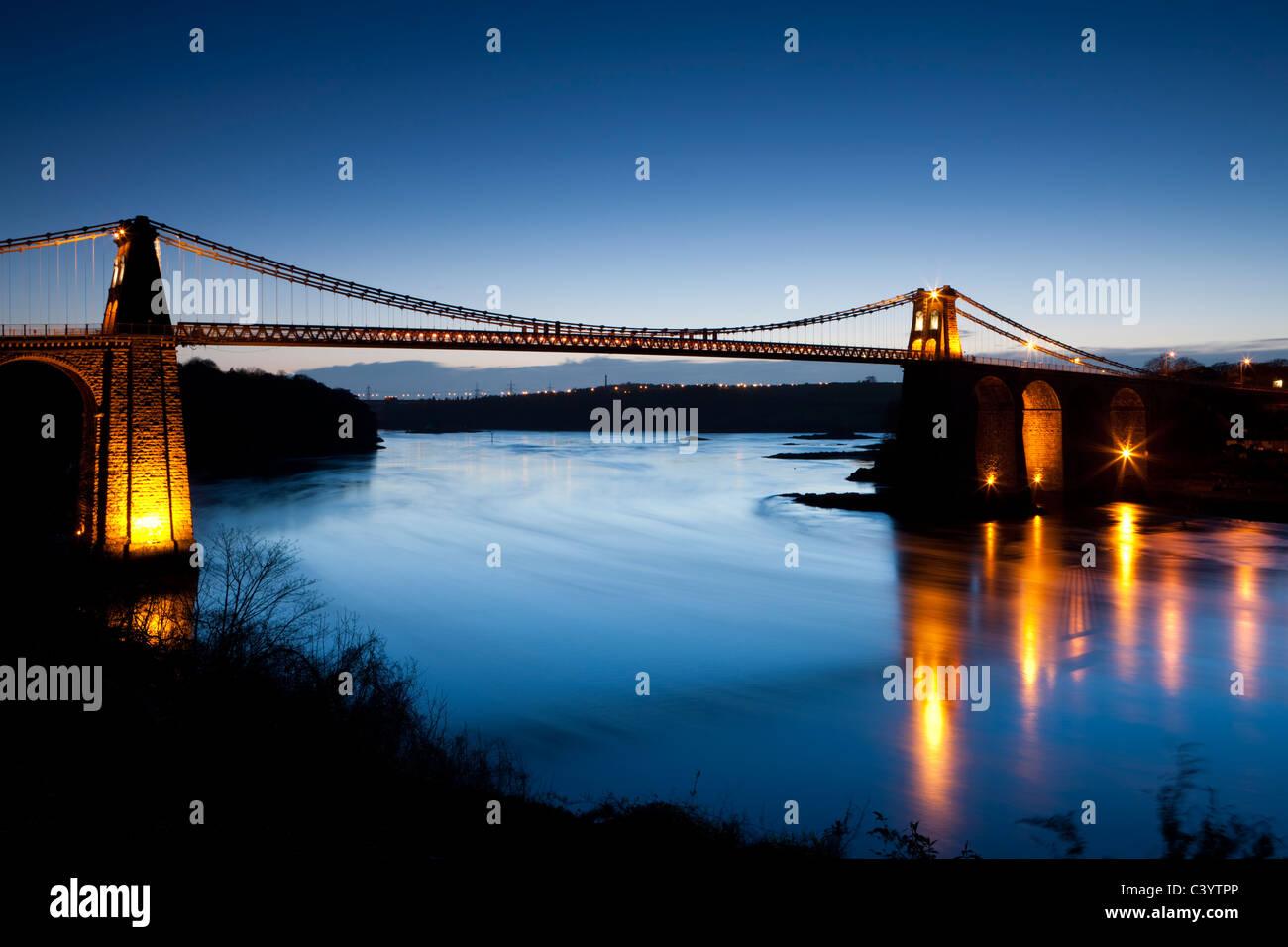 Am Abend Beleuchtungen auf die Menai-Brücke über die Menai Strait, Anglesey, North Wales, UK. Frühling Stockbild