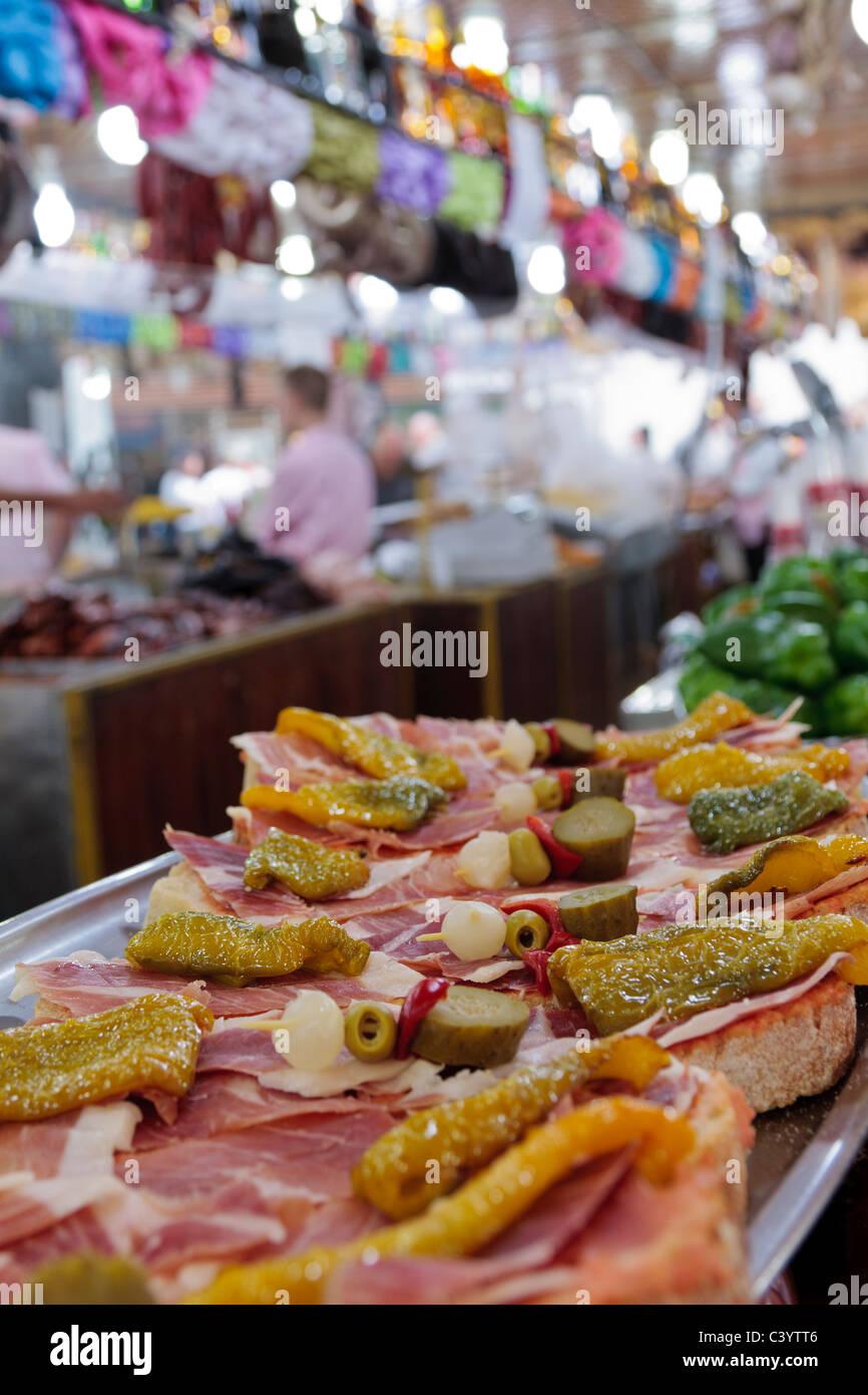 Käse und Jamon Serrano mit Gurken auf dem Display an einem Imbissstand in Santa Cruz während des Karnevals, Stockbild