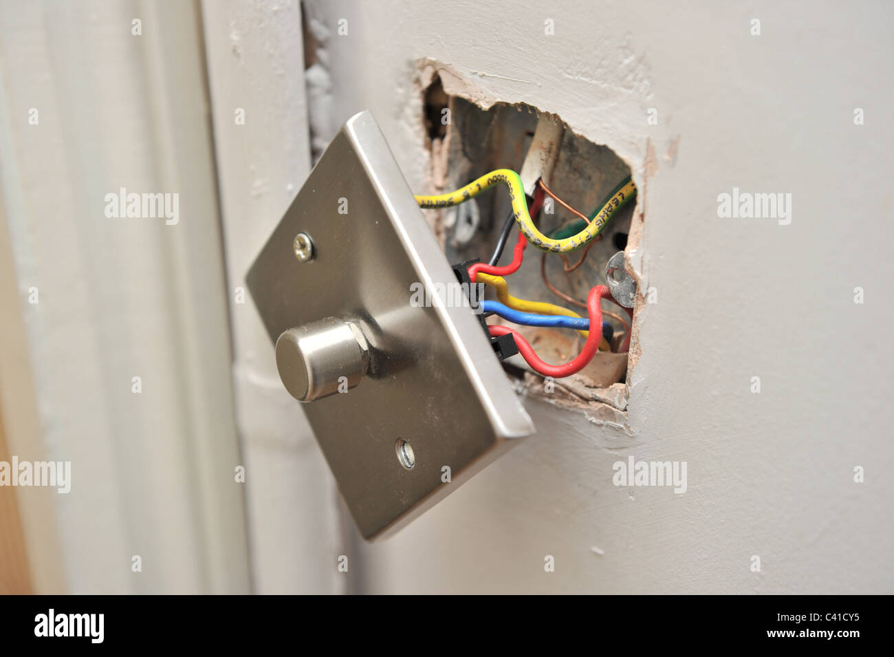 eine fehlerhafte Haus Licht dimmer-Schalter von Wand zeigt ...