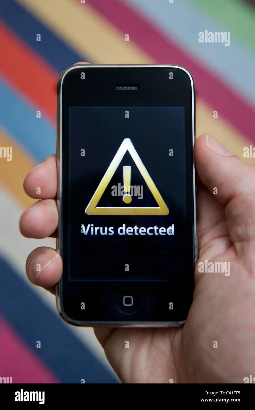 Nahaufnahme von männliche Hand, die ein iPhone, das angibt, die Entdeckung eines Virus. (Nur zur redaktionellen Stockbild