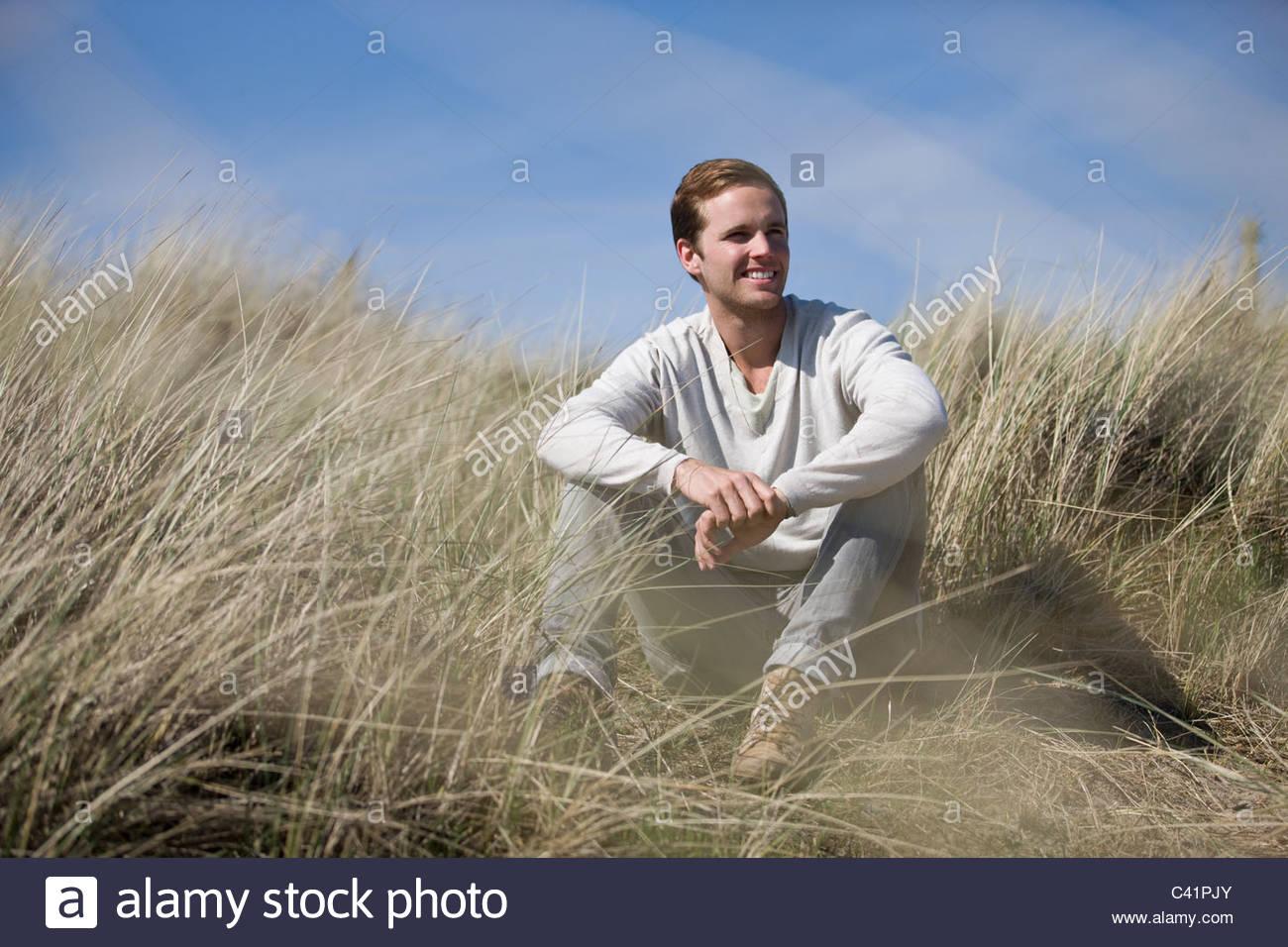 Ein junger Mann sitzt zwischen den Sand Dünen, Lächeln Stockbild