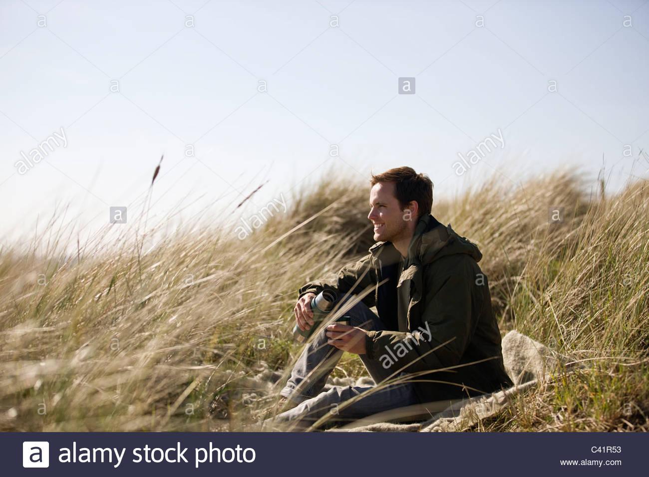 Ein junger Mann sitzt zwischen den Sand Dünen, hält eine Flasche Stockbild