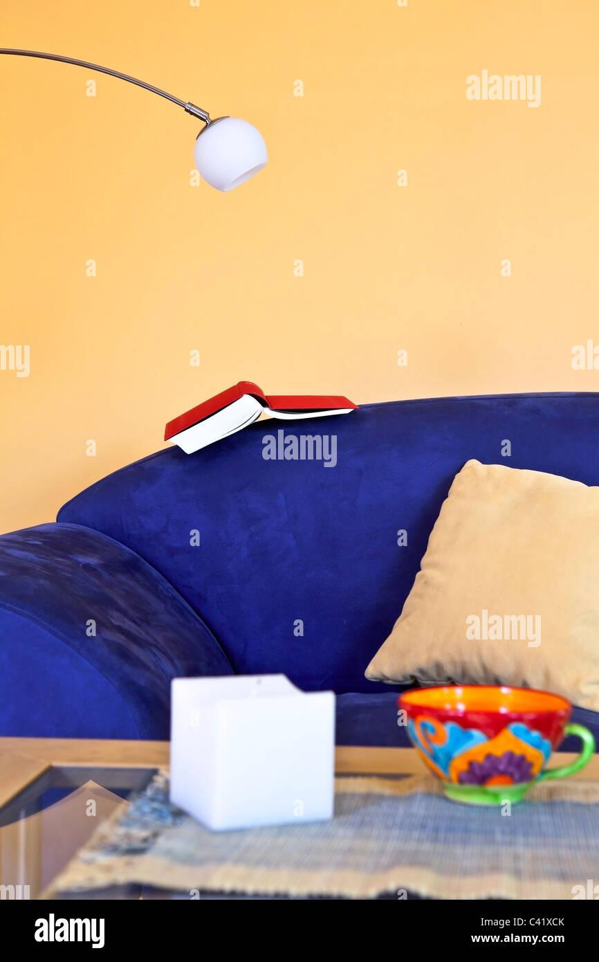 eine Leseecke mit einer blauen Couch, ein Buch und eine Leselampe Stockbild