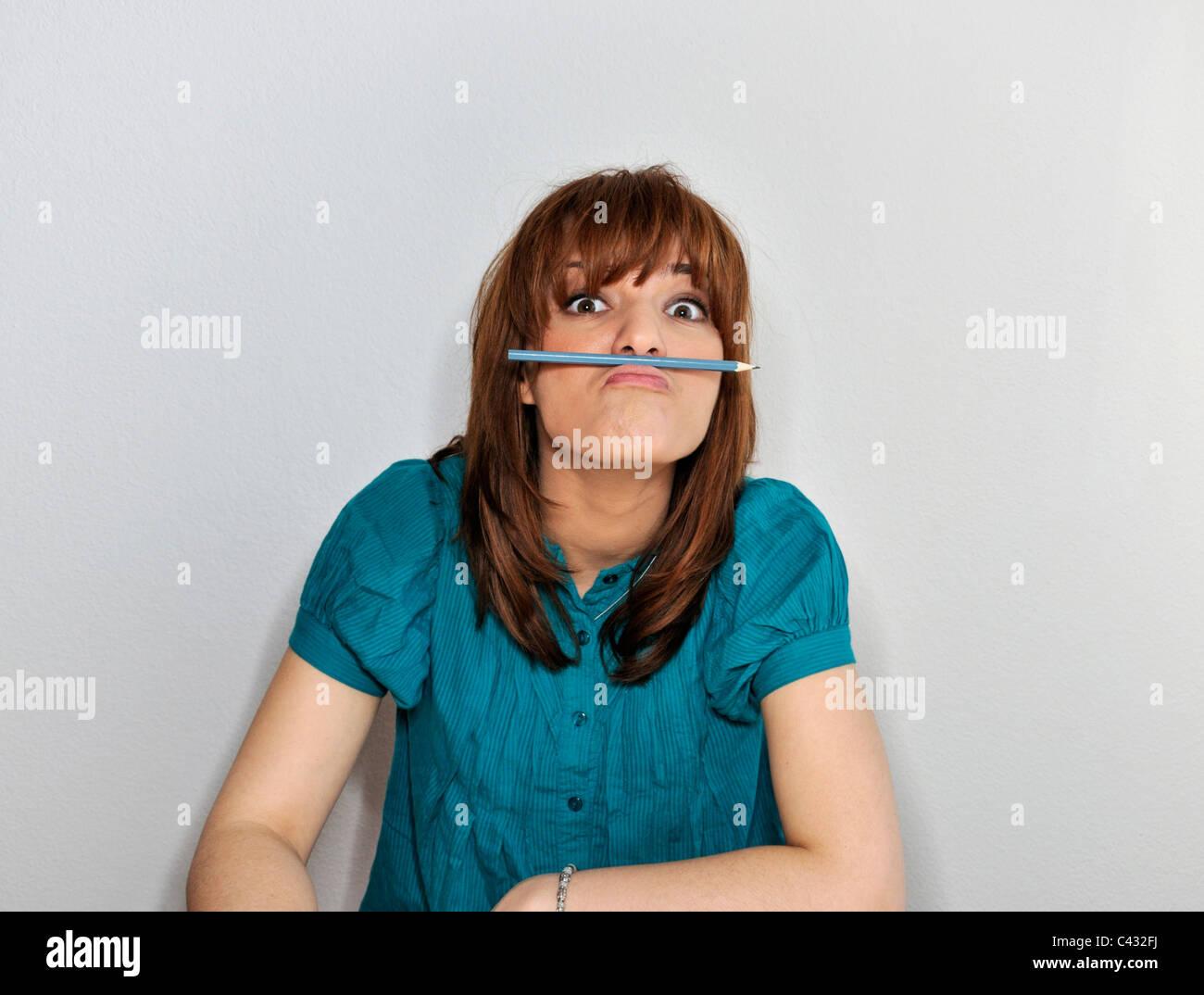 Junge Frau mit Bleistift zwischen Lippe und Nase Stockbild