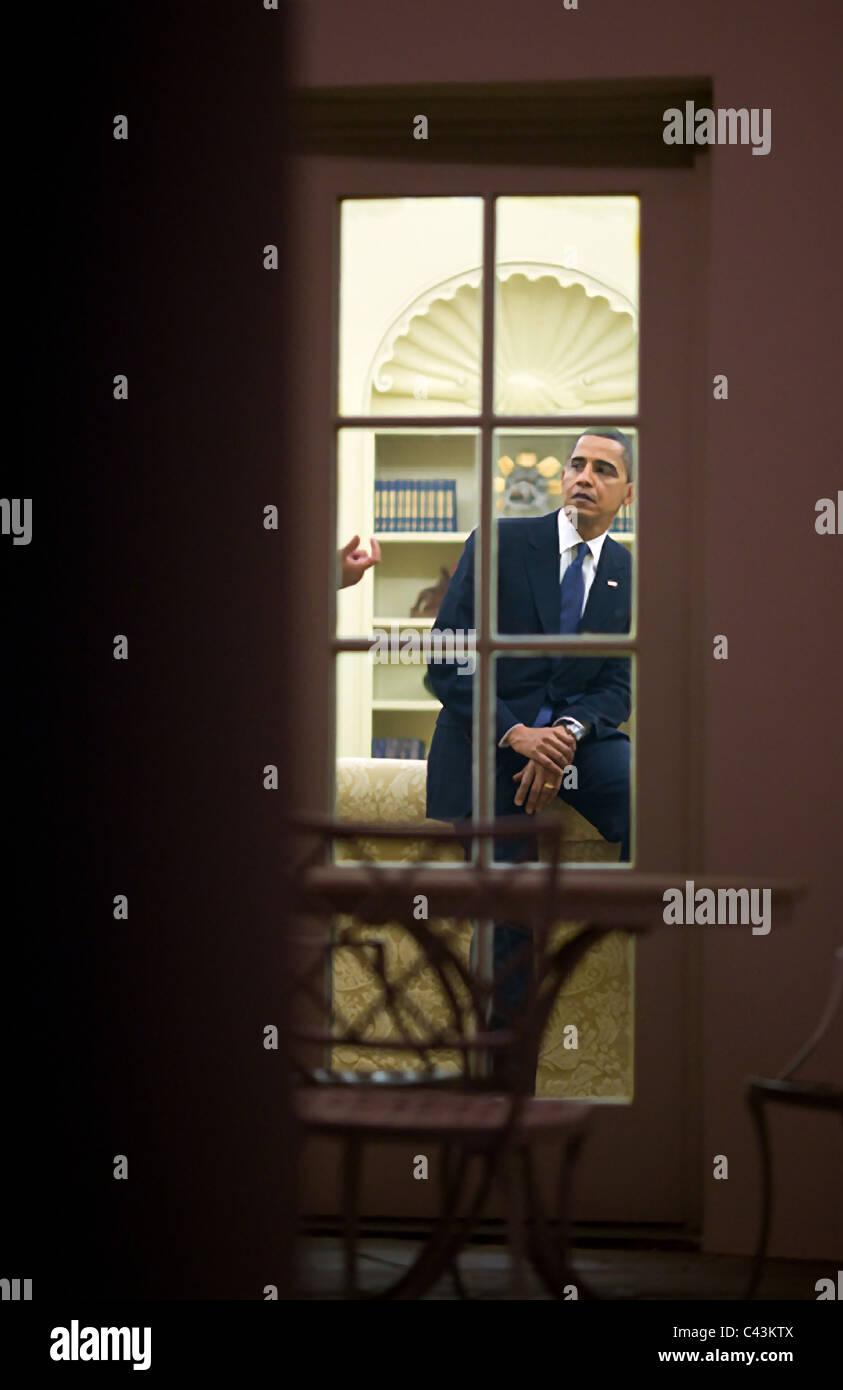 Präsident Barack Obama gesehen durch das Oval Office-Fenster während einer langen Nacht nach den Dreharbeiten Stockbild