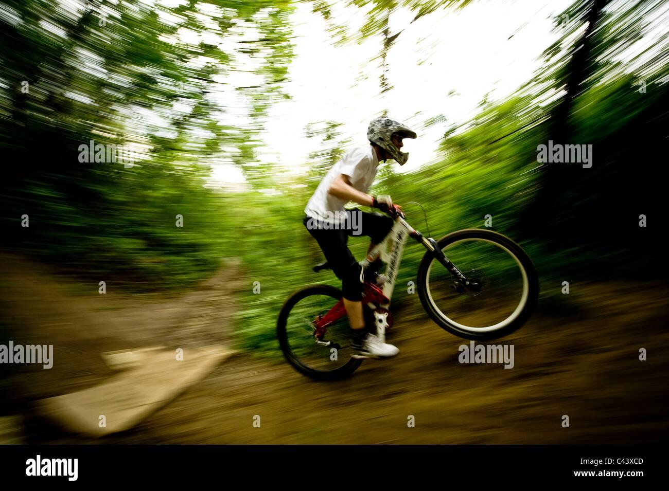 Ein junger Mann bergab Radfahren im Freien. Stockbild
