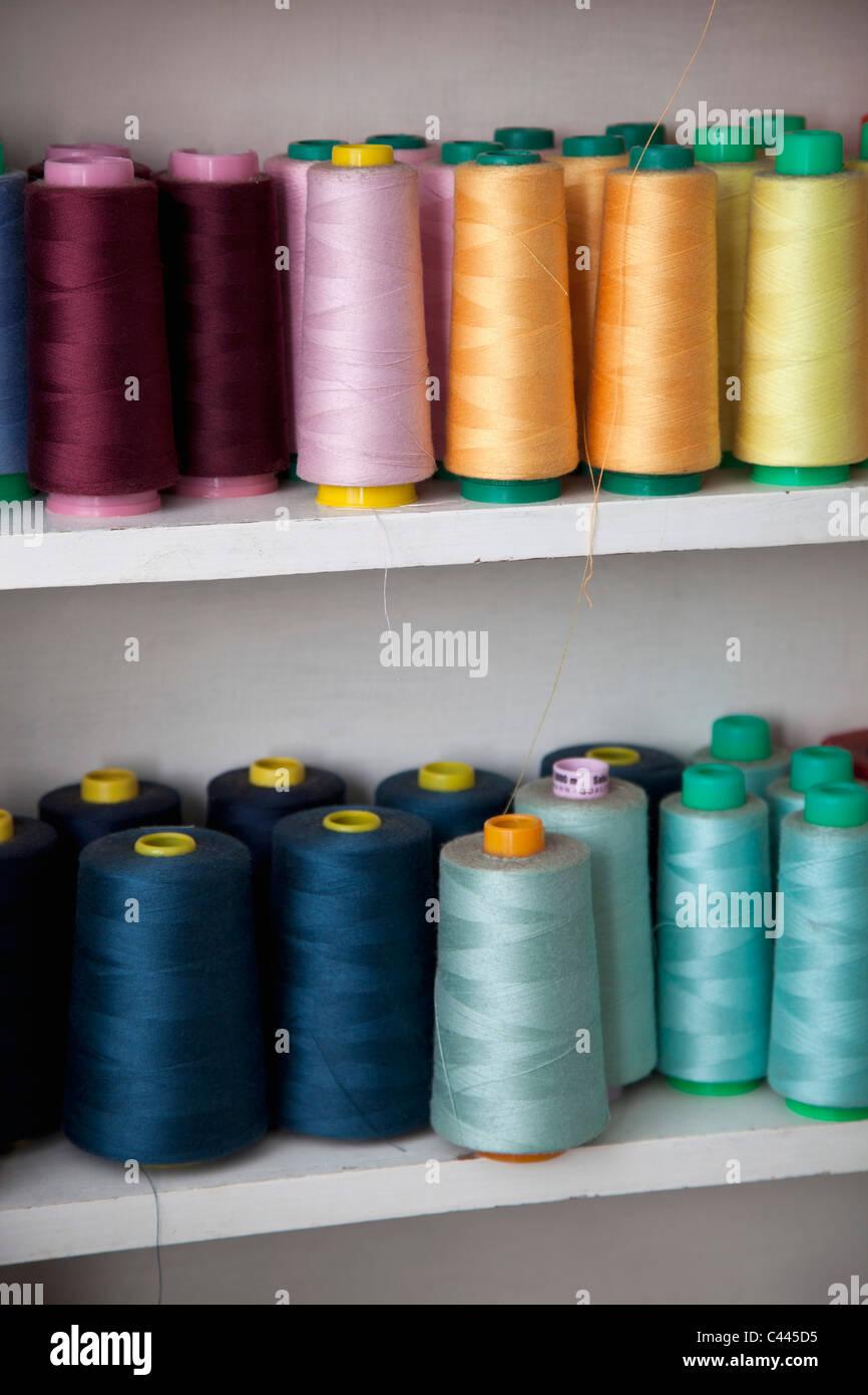 Spulen des farbigen Baumwollfaden in Regalen Stockbild