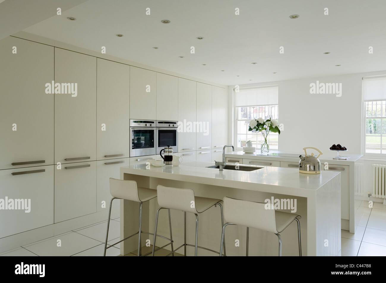 Weiße Moderne Küche Mit Corian Arbeitsplatten, Barhockern Und Einbauschränke
