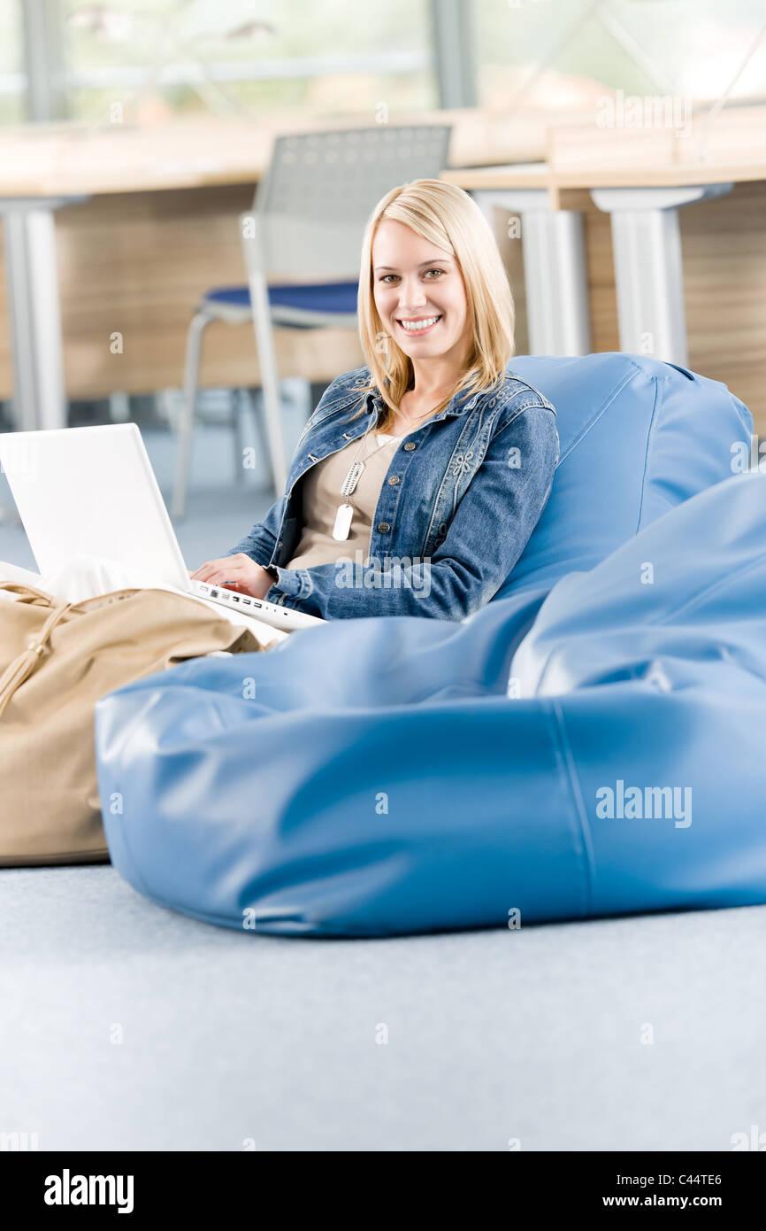 Junge glückliche Studentin an der High School entspannend mit laptop Stockbild