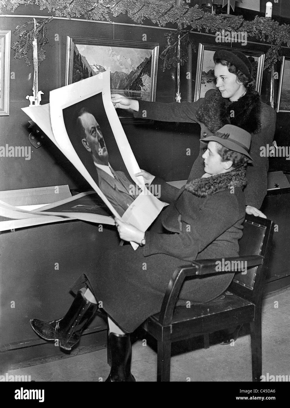 Zwei Frauen Blick auf Abbildungen, darunter ein Porträt Hitlers, 1937 Stockbild