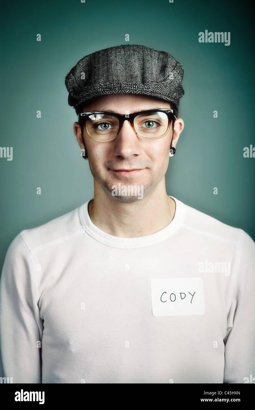 Ein hip und doch freundliche junge Mann trägt eine Mütze und Kunststoff-Gläser mit einem Namensschild. Stockbild