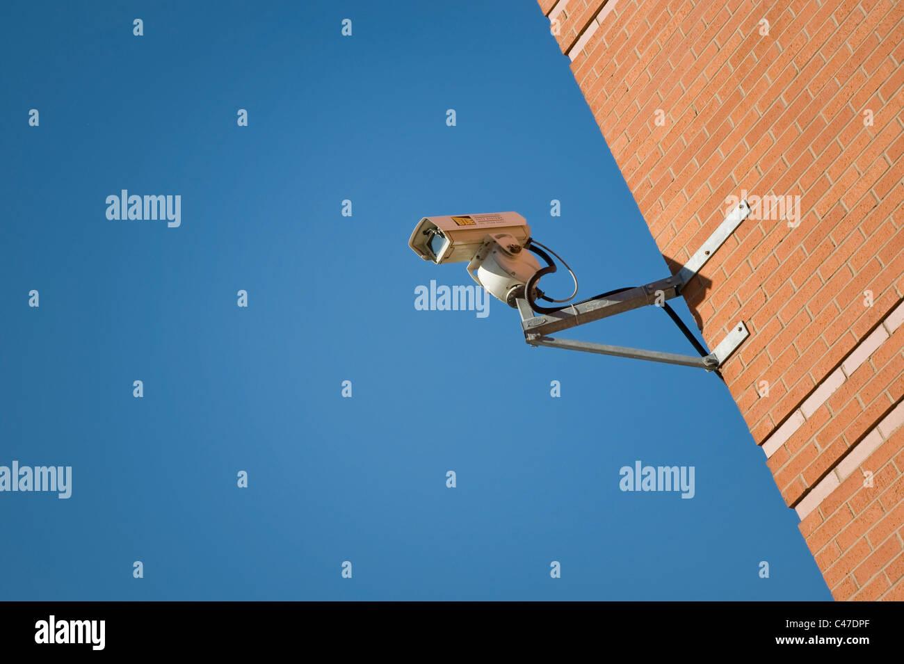 Eine CCTV-Kamera an einem hellen und klaren Himmel-Tag mit einer Mauer befestigt. Stockbild