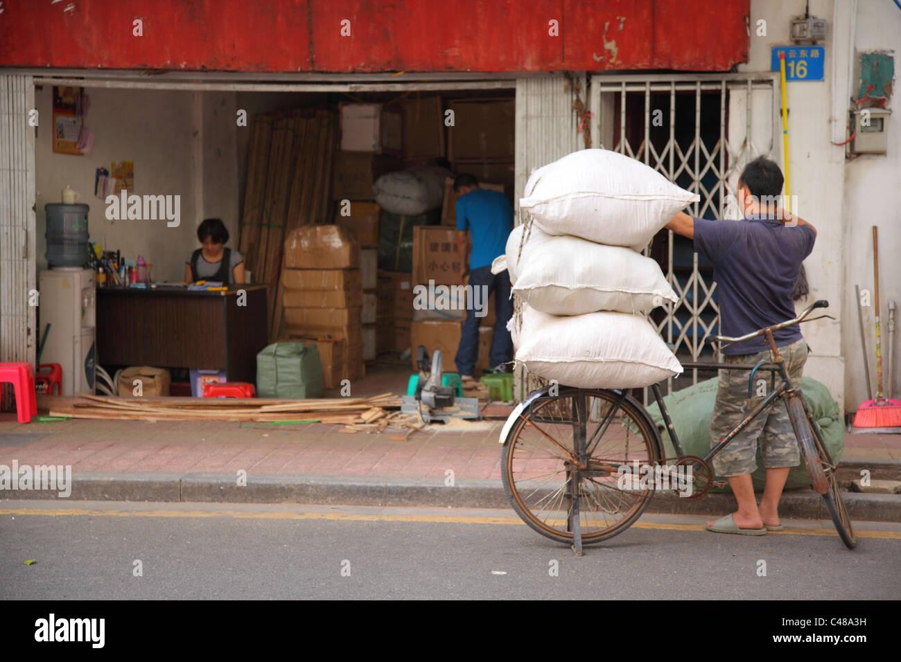Säcke des Produkts auf dem Fahrrad außerhalb Markt, Guangzhou, China Stockbild