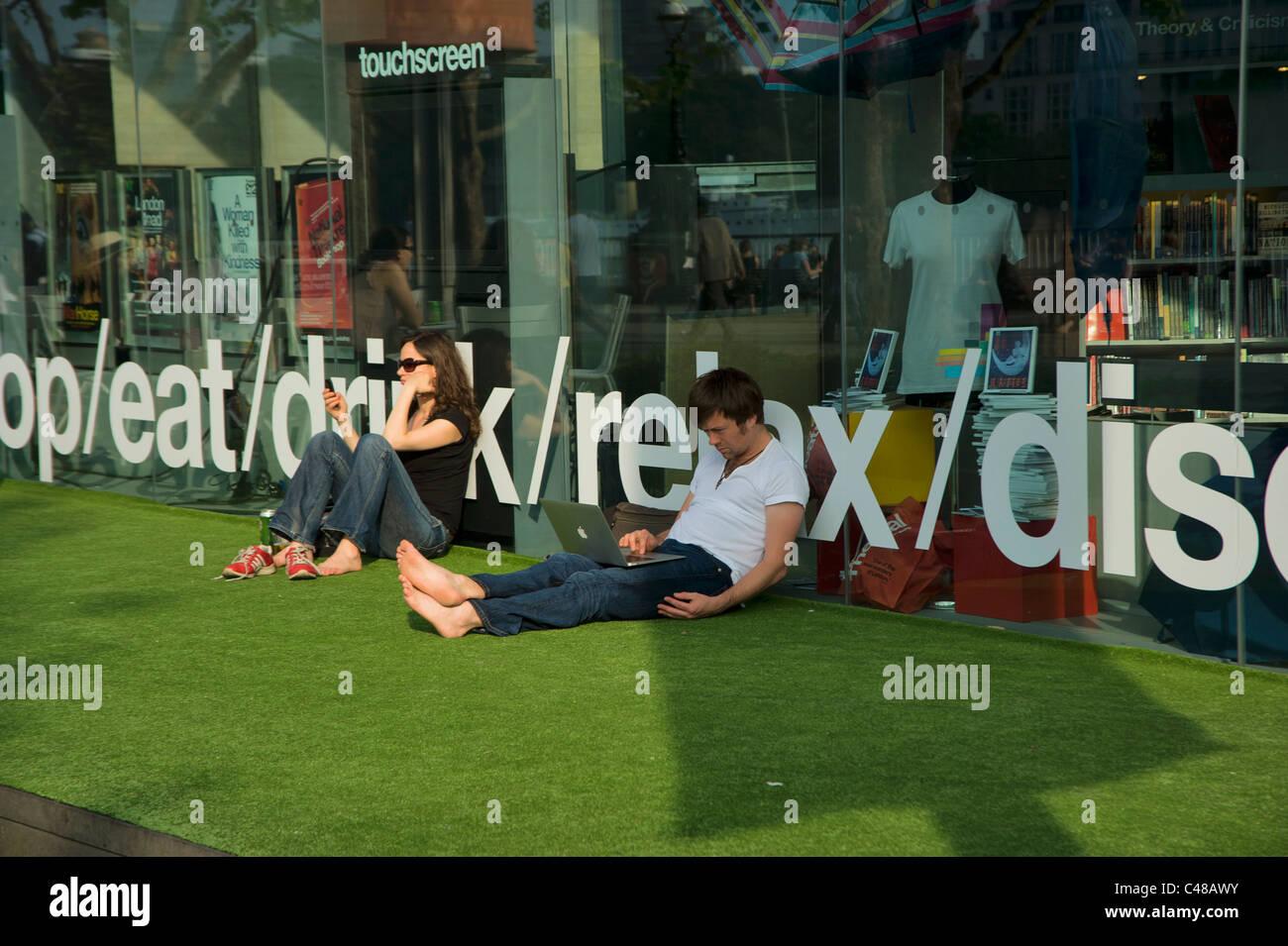 Mann und Frau, die auf der Londoner South Bank entspannen, entspannen Sie sich hinter den Worten Trinken Essen Stockbild