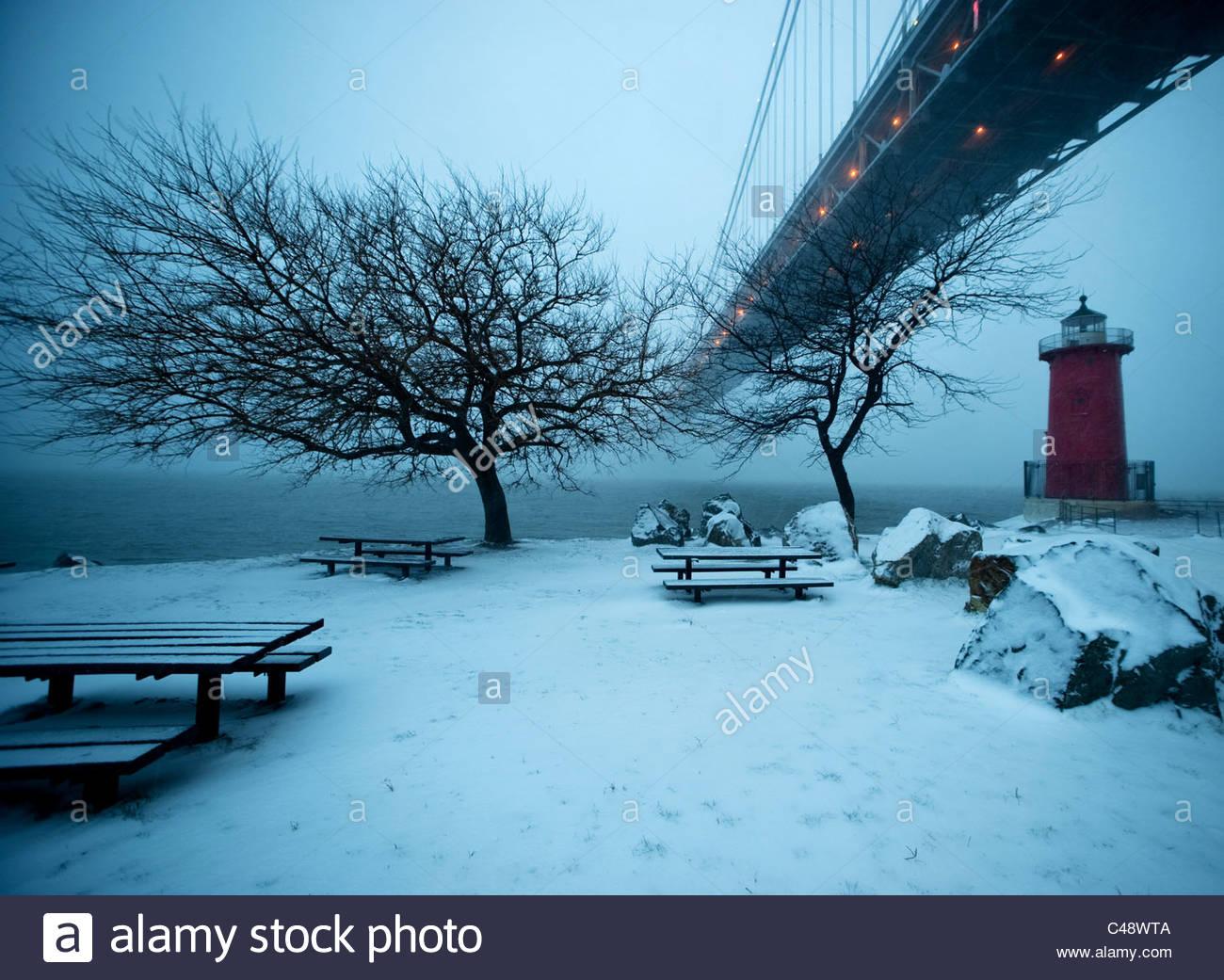 Ein kleiner roter Leuchtturm sitzt unter einer großen Brücke im Schnee in der Abenddämmerung. Stockbild