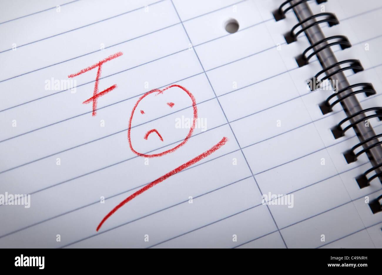 F-Klasse und eine traurige Smilie, geschrieben in roten Buchstaben in eine Spirale-Pad, shallow DOF Stockbild