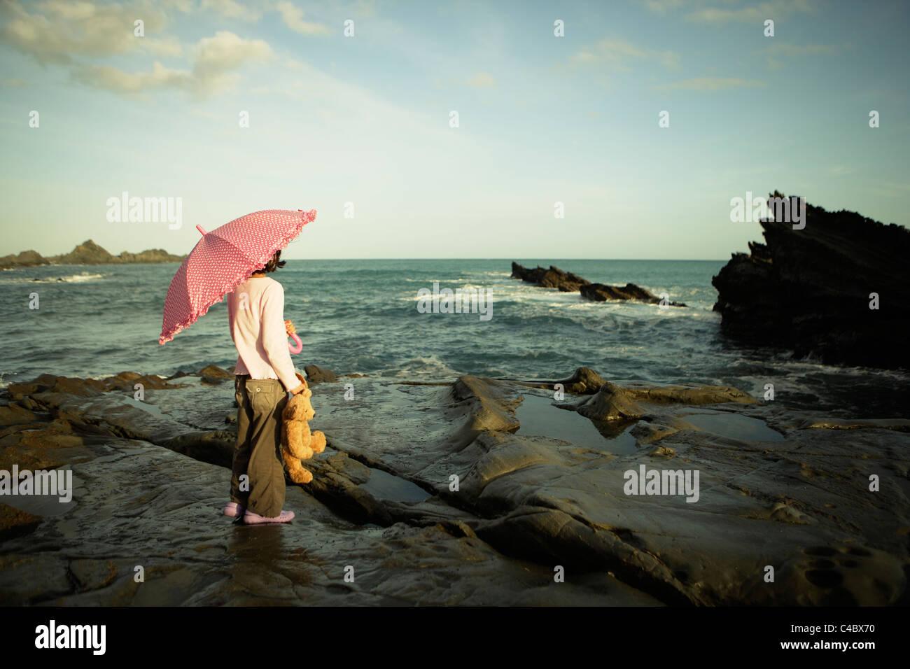 Mädchen mit rosa Regenschirm und Teddybär, Cape Palliser, Neuseeland Stockbild