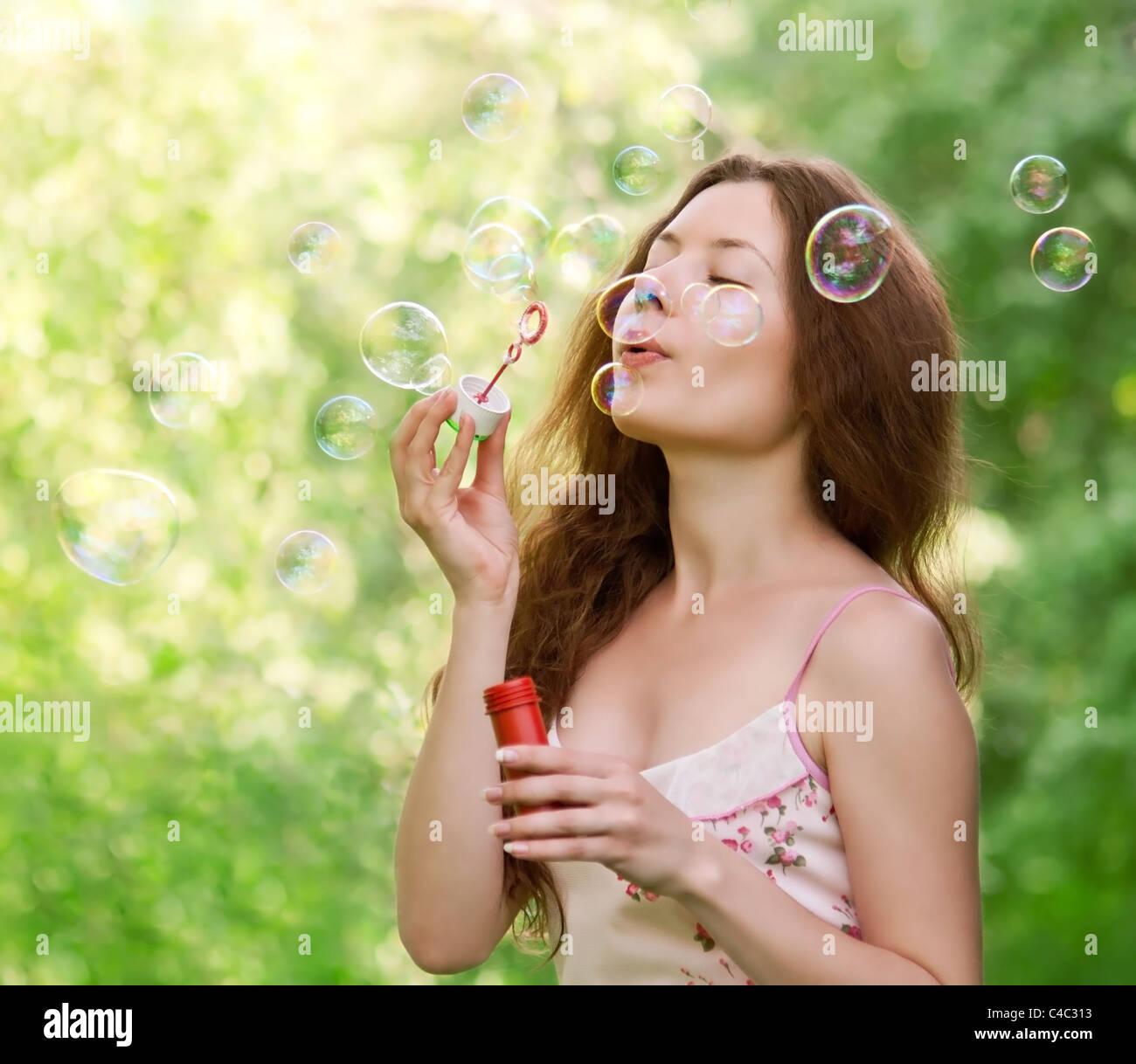 Junge schöne Mädchen bläst Seifenblasen im Park auf grünem Hintergrund Stockbild